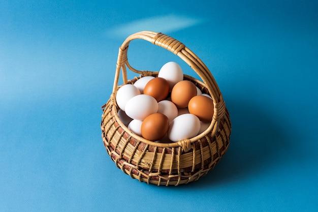 Eier in einem korb über blauem hintergrund.
