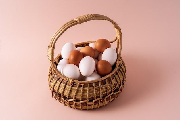 Eier in einem korb über rosafarbenem hintergrund.
