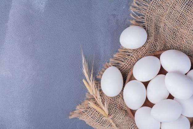 Eier in einer holzplatte auf einem stück sackleinen