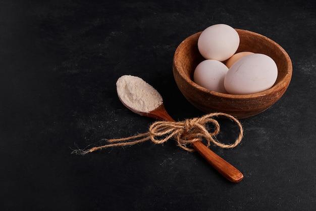 Eier in einer holzschale mit einem löffel mehl.