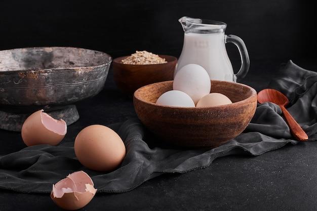 Eier in einer holztasse mit einem glas milch auf schwarzem backgorund.