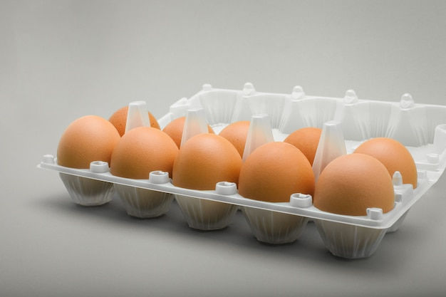 Eier in einer plastikschale, 10 stück braune hühnereier.
