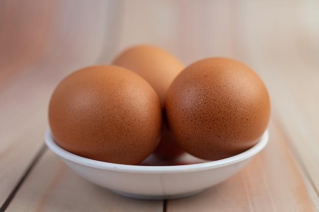 Eier in einer tasse auf einem holzboden platziert.