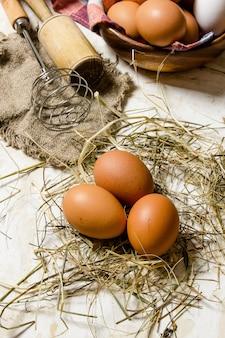 Eier in einer tasse mit heu und werkzeugen - schneebesen, stößel. auf rustikalem tisch.