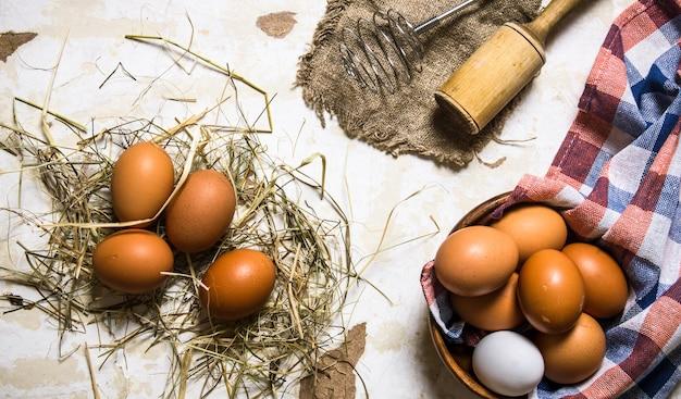 Eier in einer tasse mit heu und werkzeugen