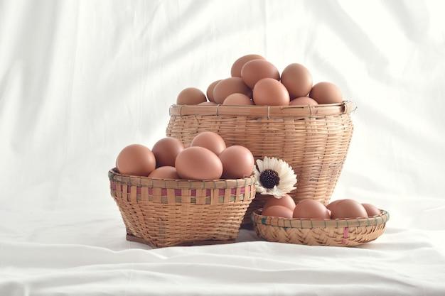 Eier in korb füllten die weinlese, die auf weißem hintergrund lokalisiert wurde