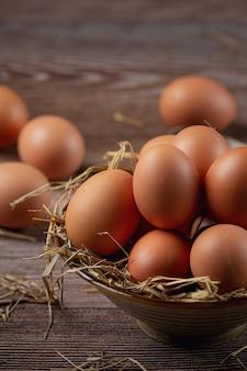 Eier in tassen auf sackleinen mit trockenem gras.