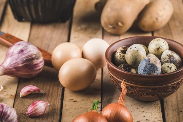 Eier, knoblauch und zwiebeln auf einem holzbrett