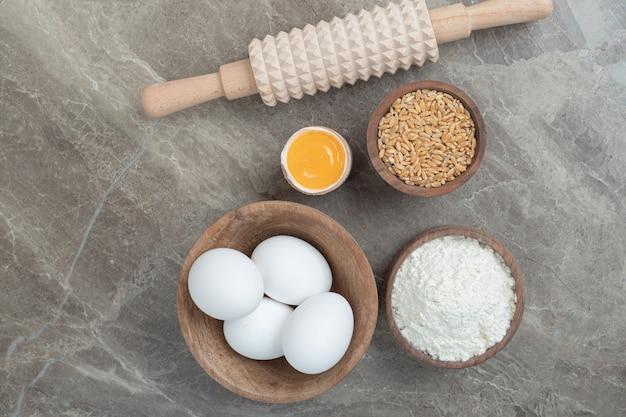 Eier, mehl, gerste und nudelholz auf marmoroberfläche. hochwertiges foto