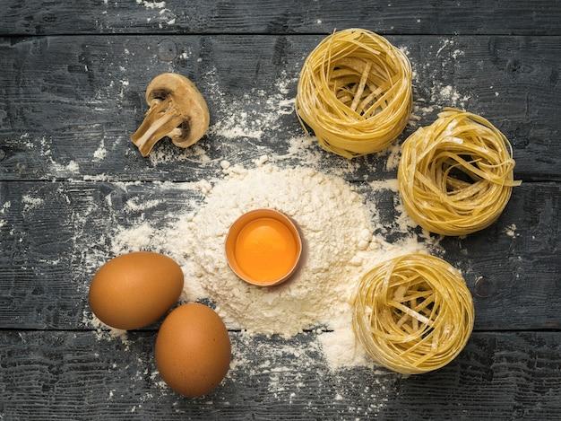 Eier, mehl, pilze und nudeln auf einem holztisch. zutaten für die herstellung von nudeln.