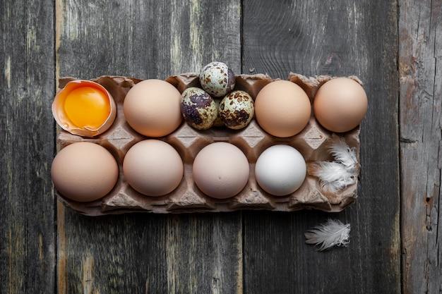 Eier mit kleinen draufsichten auf einem dunklen hölzernen hintergrund
