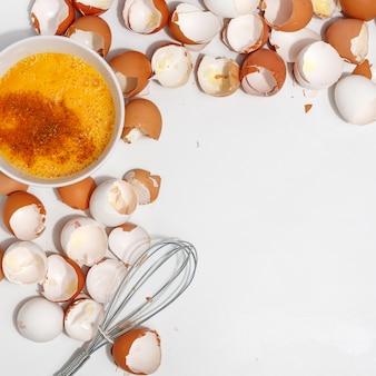 Eier mit schneebesen schlagen. eigelb und eiweiß in einer tasse. corolla eier verquirlen. zubereitung von speisen und hühnereiern. eierschale auf einem tisch. von oben betrachten.
