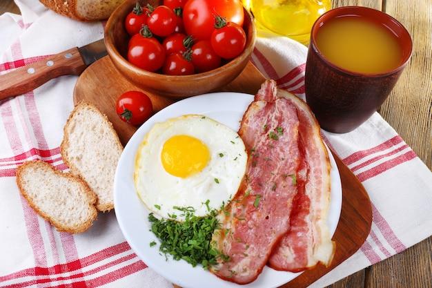 Eier mit speck und gemüse auf teller serviert