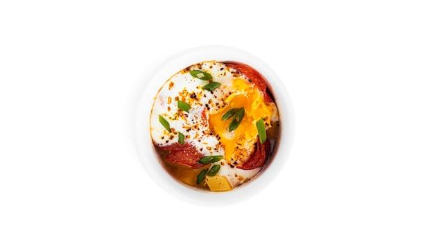 Eier mit wurst auf einem weißen hintergrund. gebackenes rührei. foto in hoher qualität