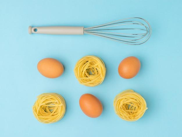 Eier, nudeln und ein schneebesen zum schlagen auf einer blauen oberfläche. zutaten für die herstellung von nudeln.