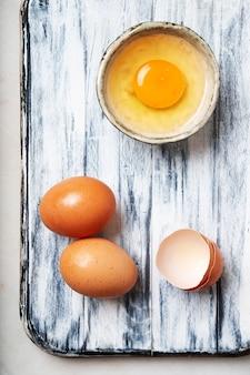 Eier über einem rustikalen schneidebrett. gebrochenes ei in winziger keramikschale. draufsicht. flache lage.