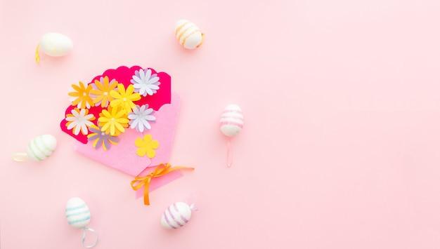 Eier und bastelblumen auf rosa hintergrund am ostertag. ostern im frühling feiern. platz für text.