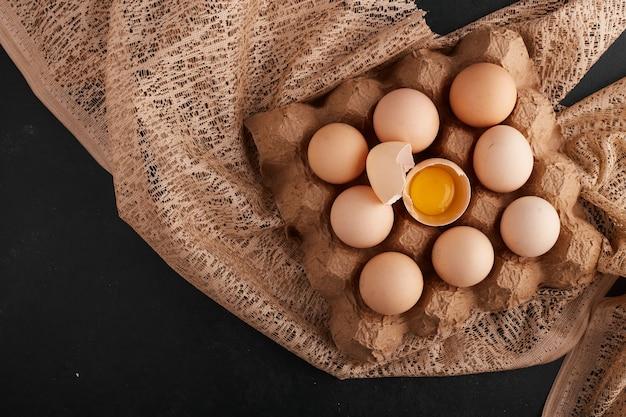 Eier und eigelb in der eierschale in der pappschale auf einem stück sackleinen.