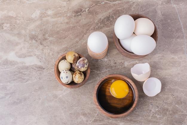 Eier und ein gelbes eigelb in einer holzschale.
