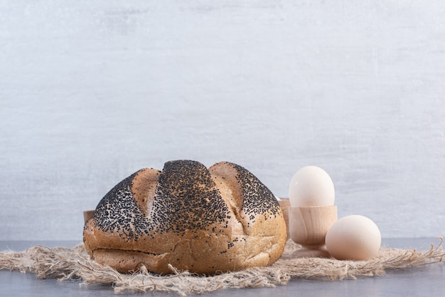 Eier und ein mit sesam überzogenes brot auf marmor.