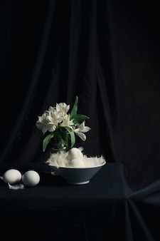 Eier und federn in der nähe von blumenstrauß