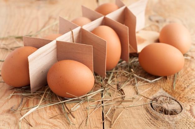 Eier und heu auf hölzernem hintergrund