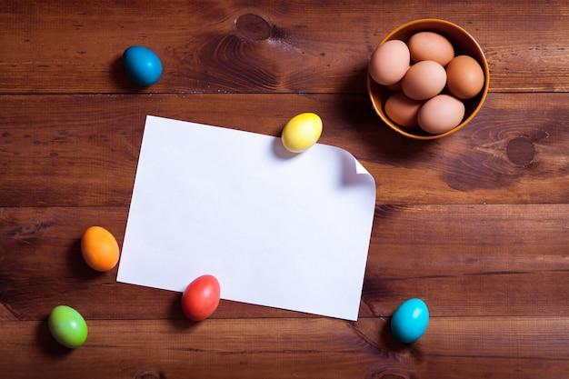 Eier und leeres weißes papier auf braunem holztisch
