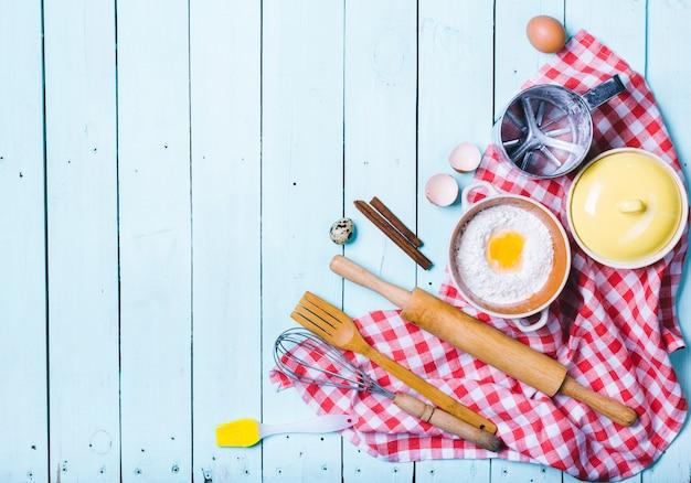 Eier und mehl mit einem nudelholz.