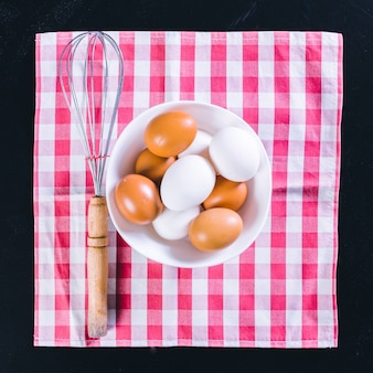 Eier und schneebesen auf einem schwarzen