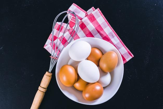 Eier und schneebesen auf schwarz