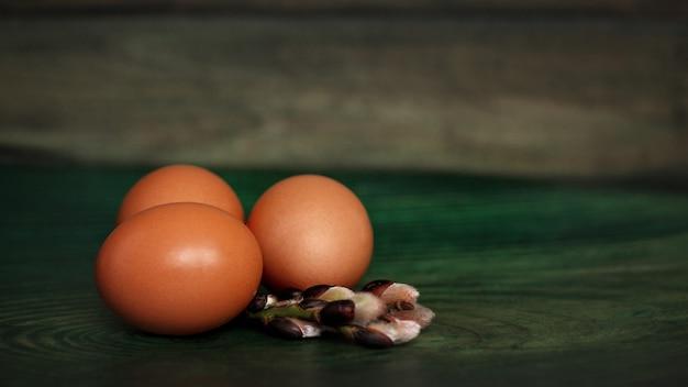 Eier und weidenniederlassungen auf einer hölzernen grünen tabelle. seitenansicht