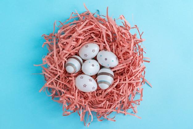 Eier verziert mit streifen, punkten und blumen im korallenroten nest auf blauem hintergrund, ostern-konzept.
