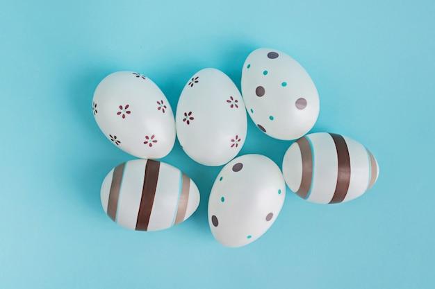 Eier verziert mit streifen und blumen auf blauem hintergrund des pasels.