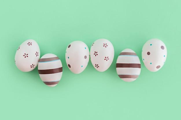 Eier verziert mit streifen und blumen auf grünem hintergrund, ostern-konzept.