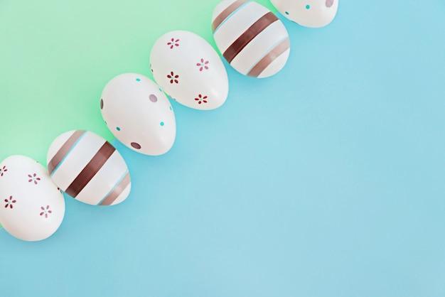 Eier verziert mit streifen und blumen auf grünem und blauem hintergrund, ostern-konzept.