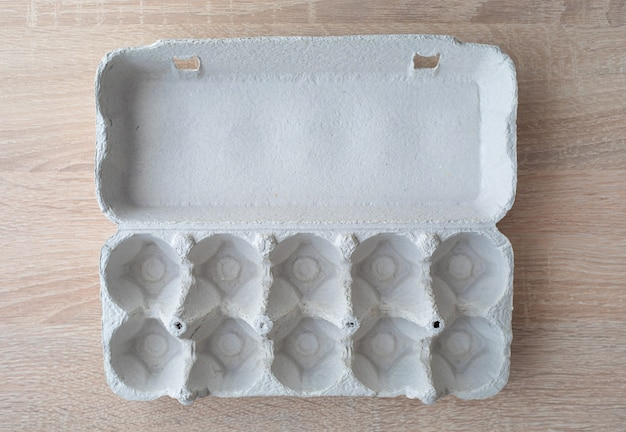 Eierkarton aus pappe. leeren eierkarton. eierbox. leere schachtel mit 10 eiern auf einem holztisch