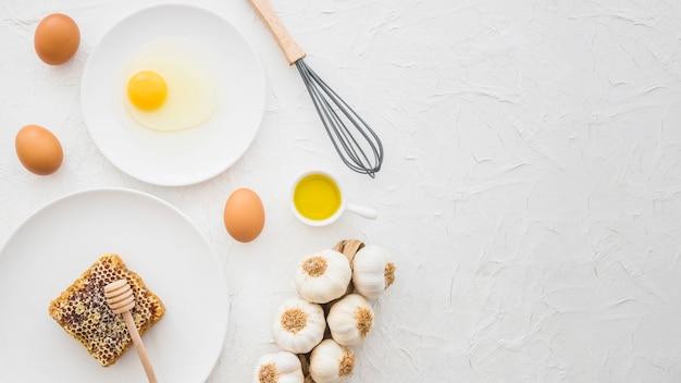 Eierkarton; eigelb; knoblauchzopf; bienenwabe und whisker auf weißem strukturiertem hintergrund