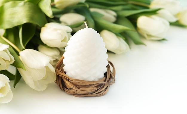 Eierkerze ostern und weiße tulpenblumen auf weiß