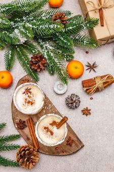 Eierlikör mit zimt und muskatnuss zu weihnachten und in den winterferien. selbstgemachtes getränk in gläsern mit scharfem rand. mandarinen, kerzen, geschenk.