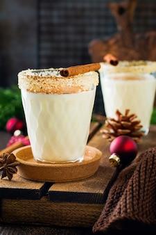 Eierlikör traditioneller weihnachtsgetränk-milchshake mit zimt auf dunklem altem tisch.