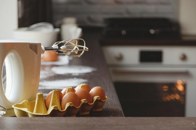 Eiermehl und mixer in der heimischen küche zum zubereiten von kuchen und desserts für die familie vor dem hintergrund ...