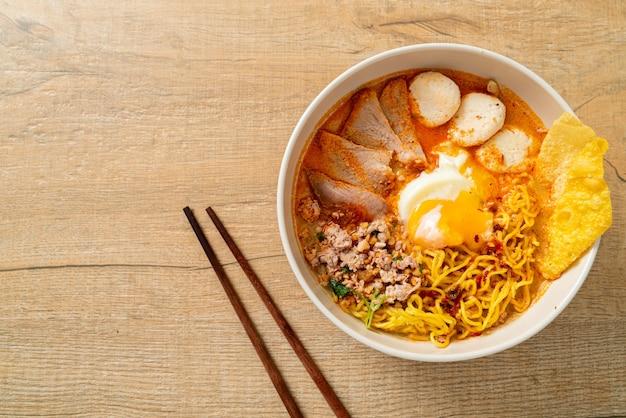Eiernudeln mit schweinefleisch und frikadellen in scharfer suppe oder tom yum nudeln nach asiatischer art