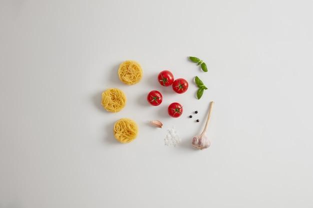 Eiernudelnester, tomaten, knoblauch, basilikumblätter, meersalz zum vorbereiten köstlicher nudeln. traditionelles italienisches gericht. essen mit viel kalorien. pflegende ungekochte nudeln und frisches gemüse