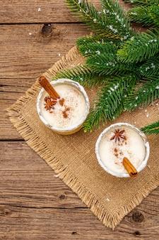Eierpunschcocktail in zwei gläsern vereinbarte mit weihnachtsdekoration auf altem holztisch. immergrüner fer baumast, künstlicher schnee, sackleinen-serviette