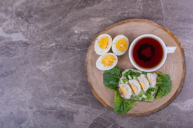 Eiersandwich mit kräutern und einer tasse tee