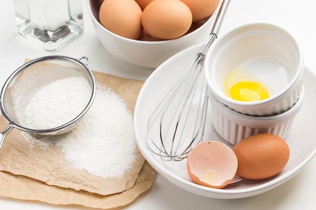 Eierschale, ei und schneebesen in einer schüssel. eigelb in schüssel. mehl und sieb auf papier. braune eier in der schüssel. weißer hintergrund. draufsicht