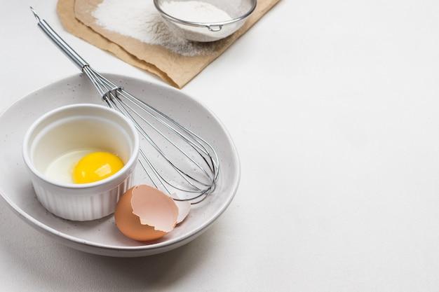 Eierschale, ei und schneebesen in einer schüssel. eigelb in schüssel. mehl und sieb auf papier.