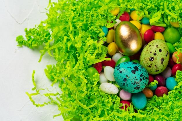 Eierschale mit bunten bonbons innen in einem dekorativen osternest