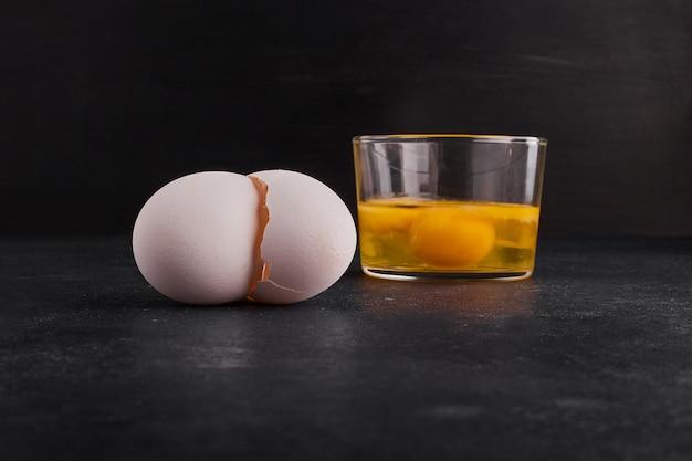 Eierschalen und eigelb in einer tasse.