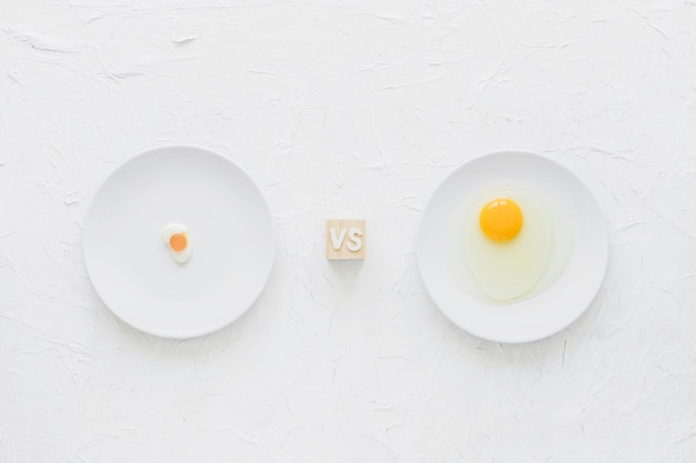 Eiersüßigkeiten gegen eigelb auf weißer platte über strukturiertem hintergrund
